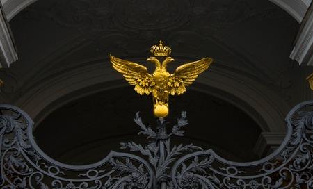 puertas de hierro: oro, �guila bic�fala, en puertas de hierro negro Foto de archivo