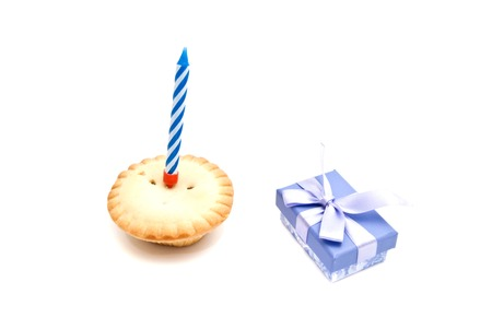 Cupcake with blue birthday candle and gift on white background
