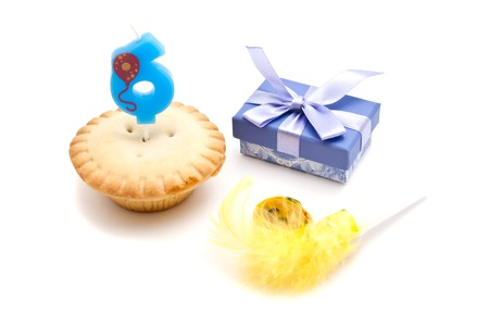 six years: cupcake with six years birthday candle, gift and whistle on white Stock Photo