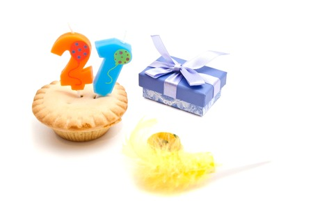 twenty one: cupcake with twenty one years birthday candle, whistle and gift on white
