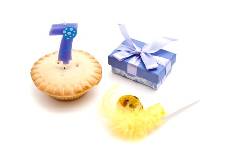 seven years: cupcake with seven years birthday candle, gift and whistle on white background