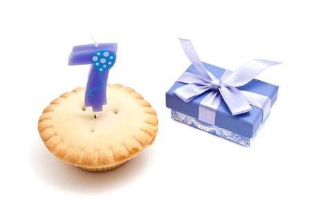 seven years: cupcake with seven years birthday candle and gift on white
