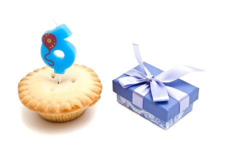 six years: cupcake with six years birthday candle and gift on white background