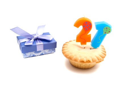 cupcake with twenty one years birthday candle and gift on white background