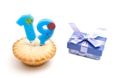 nineteen: cupcake con diciannove anni candela di compleanno e regalo su bianco
