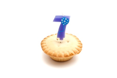 seven years: cupcake with seven years birthday candle on white background
