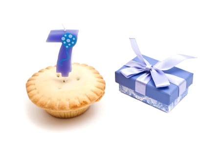 seven years: cupcake with seven years birthday candle and gift on white background Stock Photo
