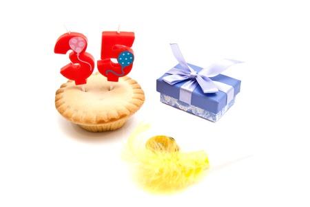 thirty five: cupcake con trentacinque anni candela di compleanno, fischietto e regalo su bianco