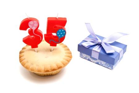 thirty five: cupcake con trentacinque anni candela di compleanno e regalo su bianco