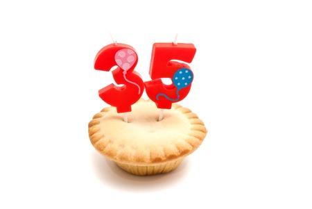thirty five: cupcake con trentacinque anni candela di compleanno su sfondo bianco Archivio Fotografico