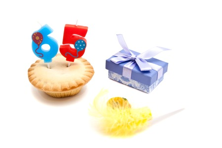 five years': cupcake with sixty five years birthday candle, gift and whistle on white Stock Photo