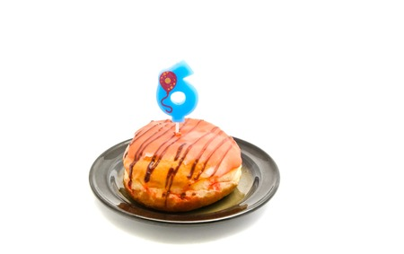six years: donut with six years birthday candle on white