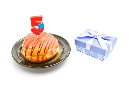 five years': donut with five years birthday candle and gift on white