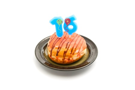 sixteen: donut with sixteen years birthday candle on white background Stock Photo
