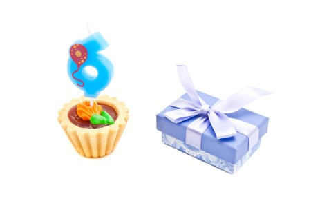six years: cake with six years birthday candle and gift on white background