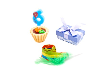 six years: cake with six years birthday candle, whistle and gift on white background