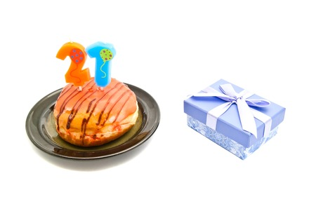 twenty one: donut with twenty one years birthday candle and gift on white background