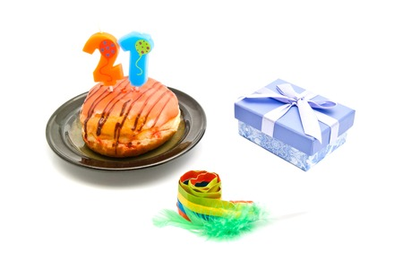 twenty one: donut with twenty one years birthday candle, whistle and gift on white background Stock Photo