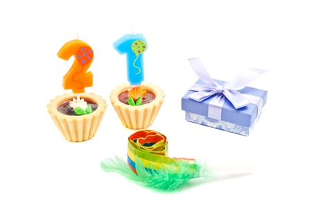 twenty one: cakes with twenty one years birthday candles, whistle and gift on white Stock Photo