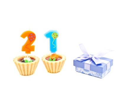 twenty one: cakes with twenty one years birthday candles and gift on white Stock Photo