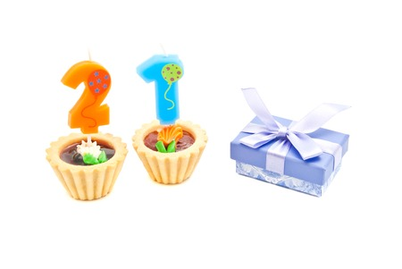 twenty one: cakes with twenty one years birthday candles and gift on white background Stock Photo