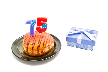 five years': donut with seventy five years birthday candle and gift on white