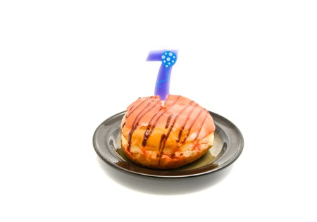 seven years: donut with seven years birthday candle on white