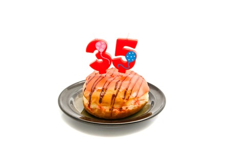 thirty five: donut with thirty five years birthday candle on white background Stock Photo