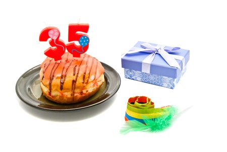 thirty five: donut with thirty five years birthday candle, whistle and gift on white