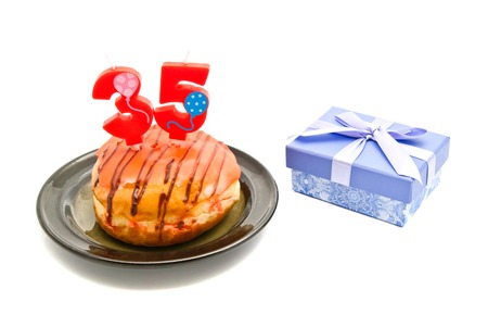 thirty five: donut with thirty five years birthday candle and gift on white