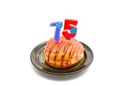 five years': donut with seventy five years birthday candle on white background Stock Photo