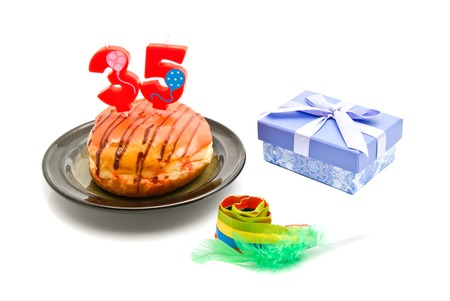 thirty five: donut with thirty five years birthday candle, whistle and gift on white background Stock Photo