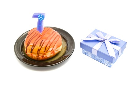 seven years: donut with seven years birthday candle and gift on white
