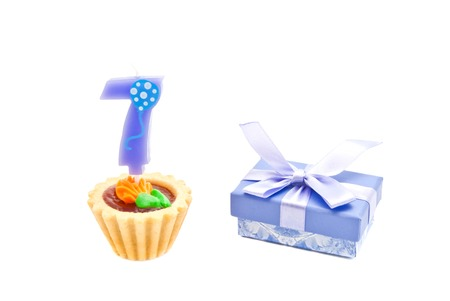 seven years: cake with seven years birthday candle and gift on white background