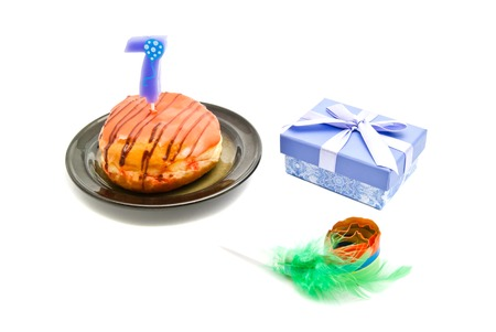 seven years: donut with seven years birthday candle, whistle and gift on white background Stock Photo