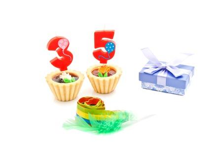 thirty five: torte con trentacinque anni le candele di compleanno, fischio e regalo su sfondo bianco Archivio Fotografico