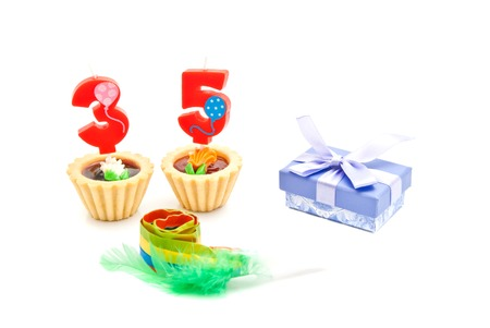 thirty five: cakes with thirty five years birthday candles, whistle and gift on white Stock Photo