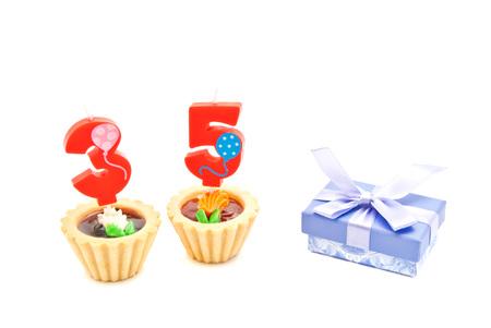 thirty five: torte con trentacinque anni di compleanno candele e regalo su bianco Archivio Fotografico