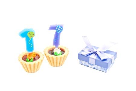 tortas de cumpleaños: pasteles con velas diecisiete años de cumpleaños y regalo en blanco Foto de archivo