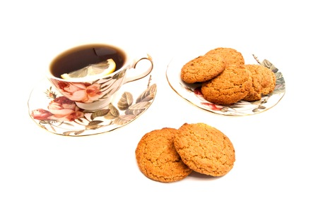 coffeecup: cup of tea with lemon and oatmeal cookies on white background Stock Photo