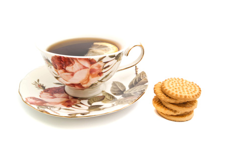 coffeecup: cookies and cup of tea with lemon on white closeup