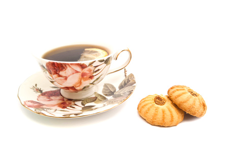 cookies and cup of tea with lemon on white background