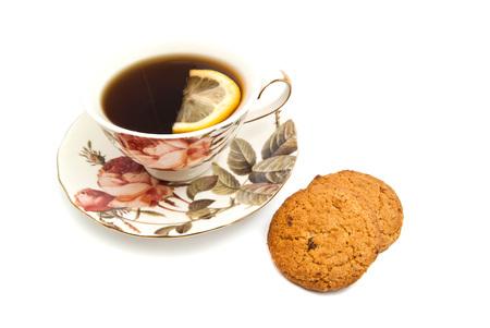 coffeecup: oatmeal cookies and mug of tea with lemon on white