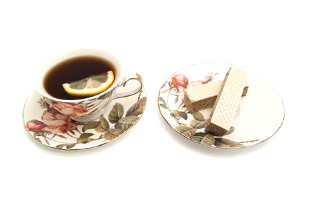 coffeecup: wafer and cup of tea with lemon closeup on white