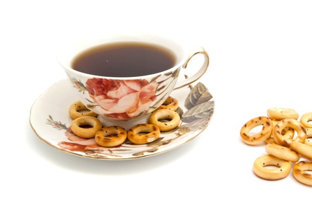 some bagels and cup of tea on white background