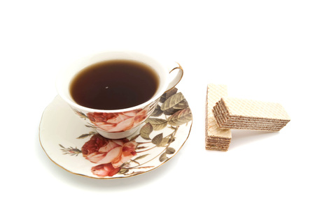 coffeecup: pair of wafers and cup of tea closeup on white