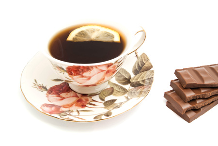 coffeecup: cup of tea with lemon and chocolate closeup on white