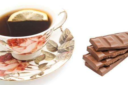 coffeecup: cup of tea with lemon and chocolate on white closeup