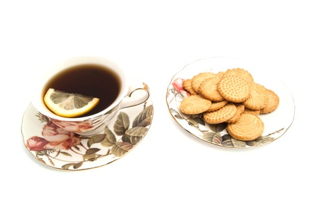 cup of tea with lemon and tasty cookies on white closeup