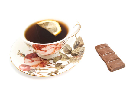 coffeecup: cup of tea with lemon and chocolate on white